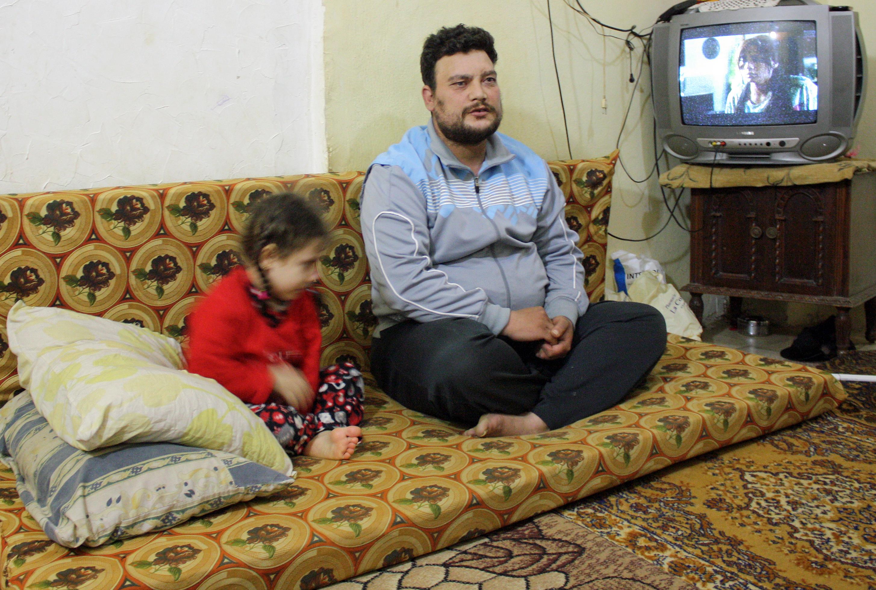 Ayman-pechowiec z córką, w zajmowanej przez rodzinę suterenie w Trypolisie/fot. Marcin Ogdowski