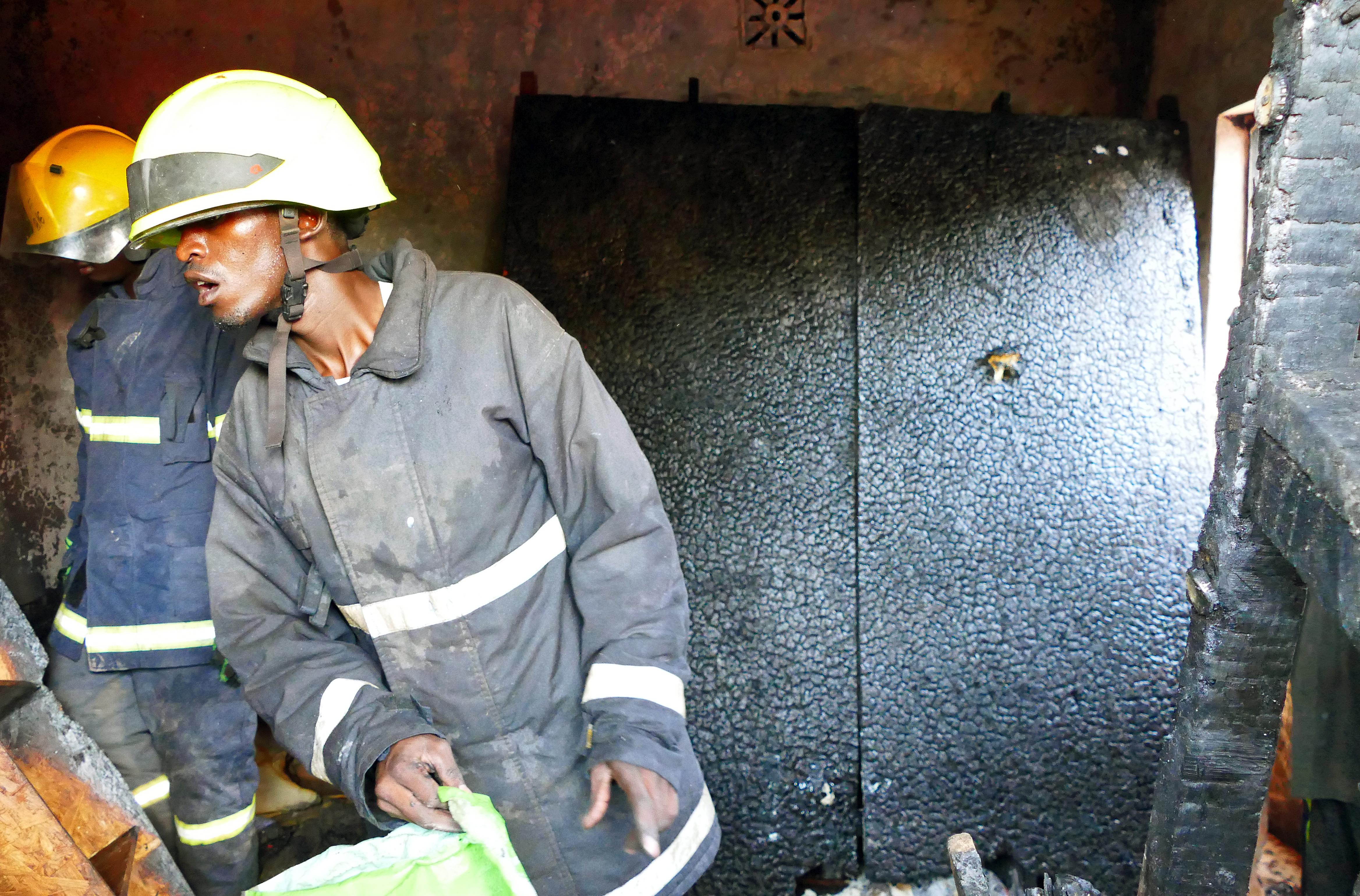 Strażacy podczas przeszukania spalonego mieszkania w slumsowisku w Thika/fot. Marcin Ogdowski